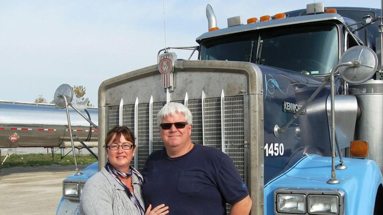 smiling man and woman in front of a large truck