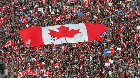 Crowd holds a very large Canadian flag.
