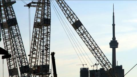 construction cranes in front of CN Tower in Toronto