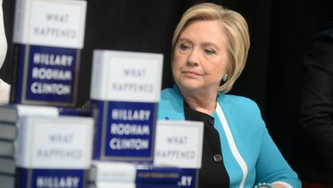 Hillary Clinton posing with her book, What Happened?