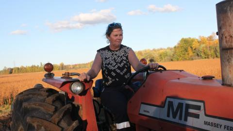 a woman on a tractor on her farm