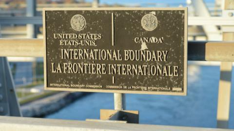 "a sign at a border crossing saying, ""International Boundary"""