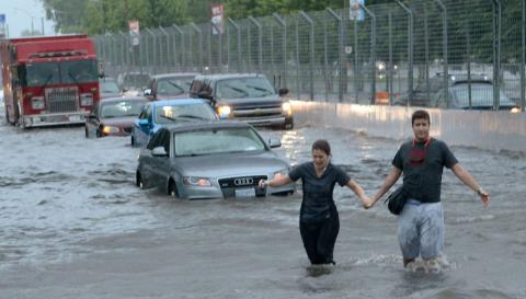 two people walking away from their car during a flood in Toronto