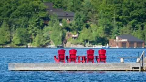 Muskoka chairs on a dock on a lake