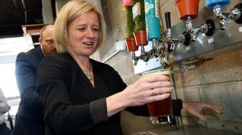 Alberta Premier Rachel Notley pouring beer