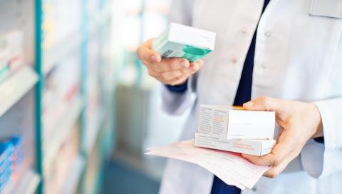 Pharmacist's hands hold boxes of medications.