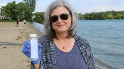 a person holding up a water sample by the lake