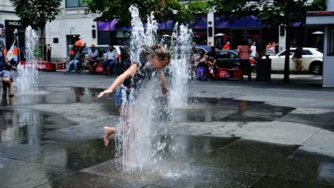a child runs through a city fountain in Toronto during a heat wave