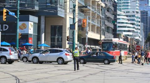 a police officer guides traffic in Toronto