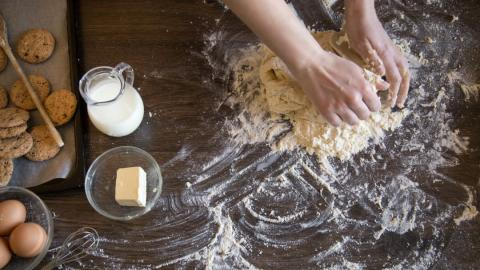 a baker kneading dough surrounded by ingredients such as butter, milk and flour