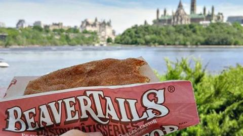 a person holding up a beavertail pastry with the Parliament buildings in Ottawa in the background