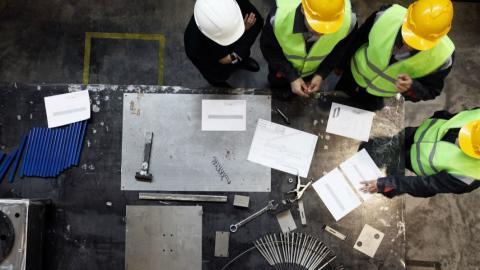 men in hard hats stand at a table looking at construction plans