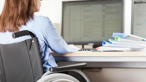 a woman using a wheelchair at a computer