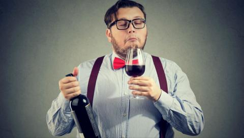a person smelling wine