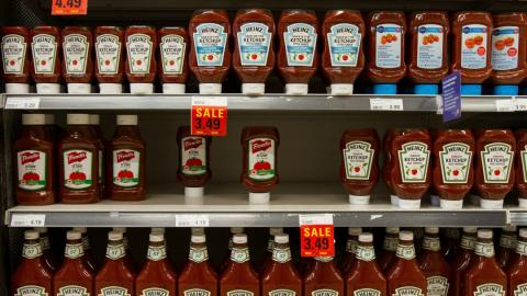 Ketchup bottles on a grocery store shelf.