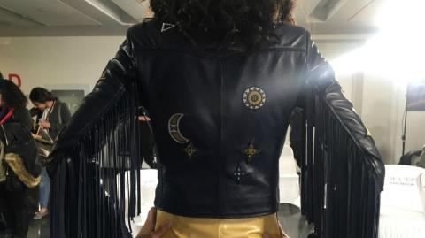 A woman modeling the back of a leather jacket