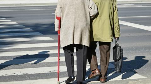 an older couple walking across the street
