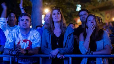 men and women outdoors watching a concert