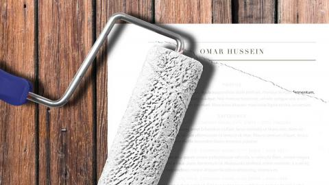 a resume with a paint brush wiping over it in white