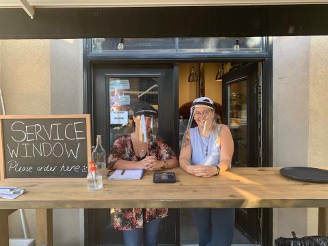 Two women wear face shields outside a restaurant