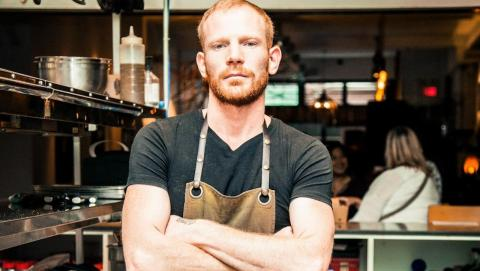 man with apron and arms crossed standing in front of diners