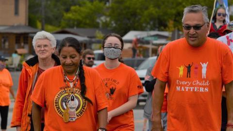 people walking in orange shirts