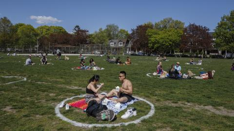 small groups of people sit in chalk circles drawn on grass