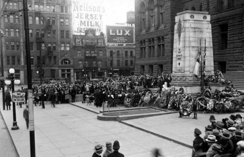 Black and white photo of people gathered in front of a large building.
