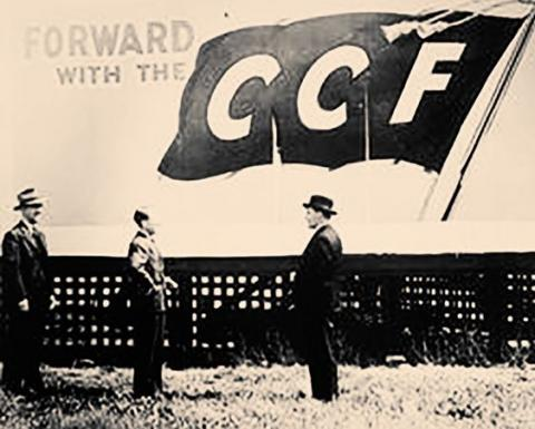 Black and white photo. Three men stand in front of a banner.