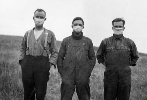 archival photo of three men wearing masks during Spanish Flu pandemic