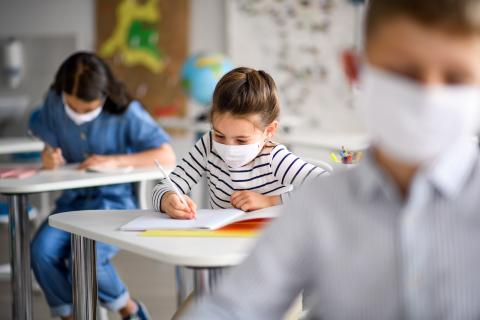 three children wearing masks while working in a classroom