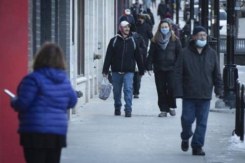 masked people walk down a street