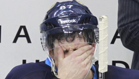 a hockey player holds his hand over his face