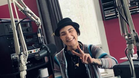 smiling woman in a hat makes a peace sign beside a microphone