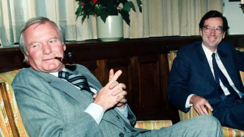 two men in suits smiling, one holding a pipe