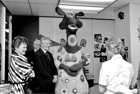 a group of people stand with a large mascot