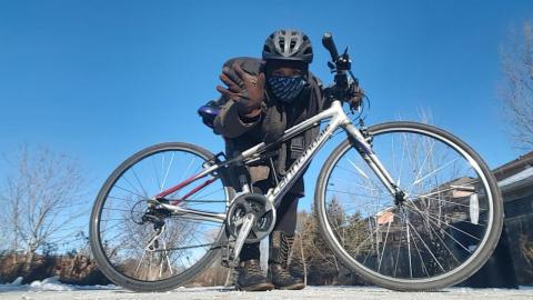 a masked woman leans over a bike