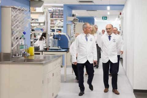 two men in white coats walk through a lab