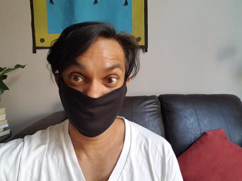 a man sitting on a couch wearing a mask
