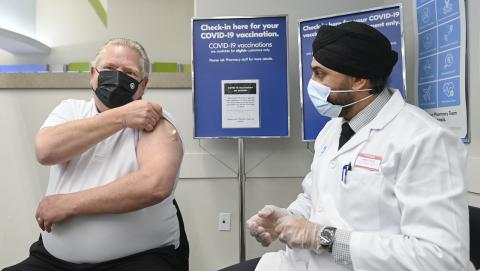 a masked man rolls up his sleeve to receive a shot from a health worker in PPE