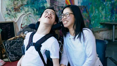 Young man in wheelchair smiles as woman sits next to him, looking at him and smiling