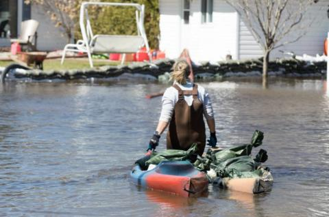 A woman brings sandbags in a kayak to her home during a flood.