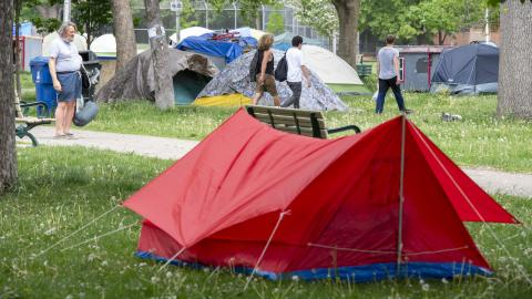 people walk through a park that features a number of tents