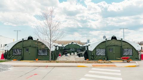two large army-green tents in a parking lot