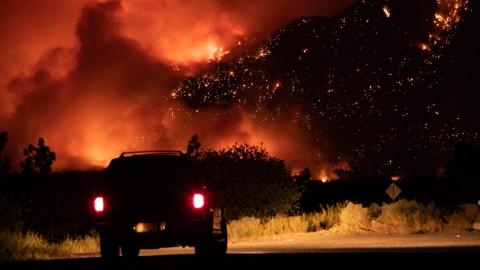 a truck in front of a massive wildfire