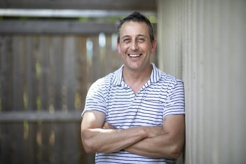 a smiling man with arms crossed wearing a T-shirt