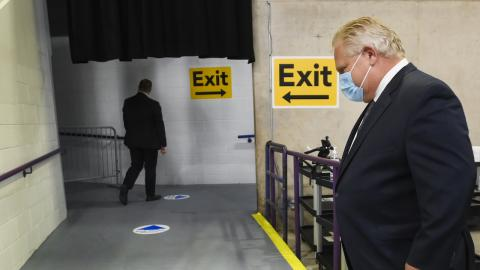 """masked man in suit walks past yellow """"exit"""" sign"""