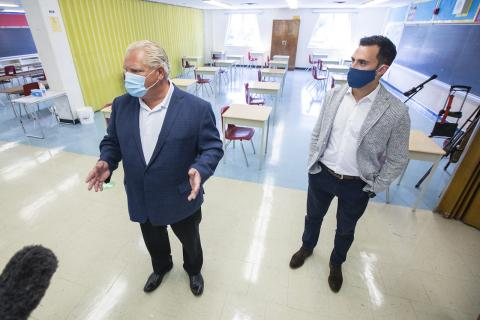 two men wearing suits and masks stand in a classroom
