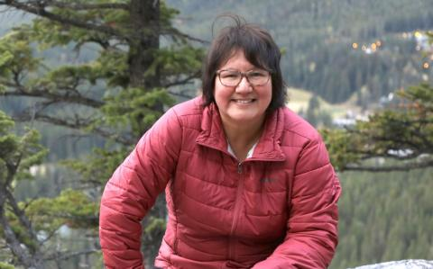 Melanie Goodchild looks at the camera in a red jacket