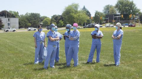 a group of health-care workers in a field wearing PPE